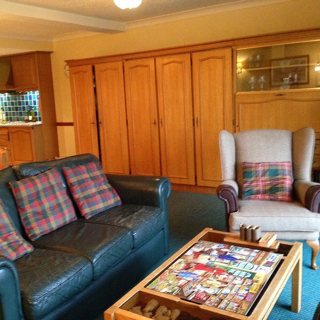 The lodge has an open plan living area, with comfy sofas and chair. The best bit is looking through the french windows for a panoramic view of Loch Ard.